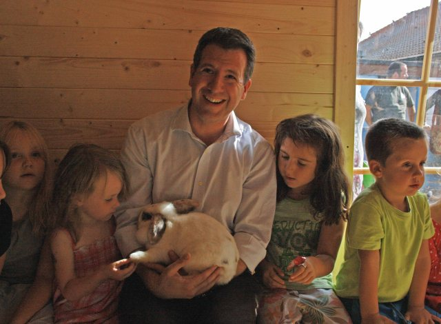 Chris Leslie MP and children meeting the farm's rabbits.